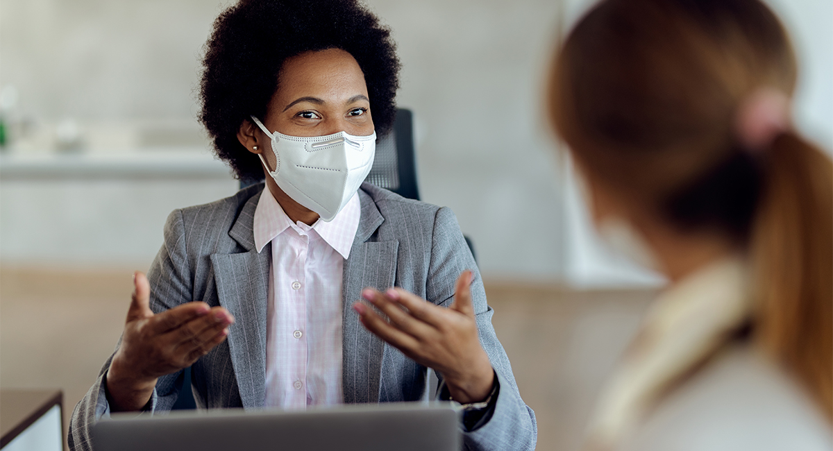 A female lawyer meets her new client, both in masks.