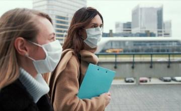 Two female legal volunteers women wearing face masks, walking on a city street.