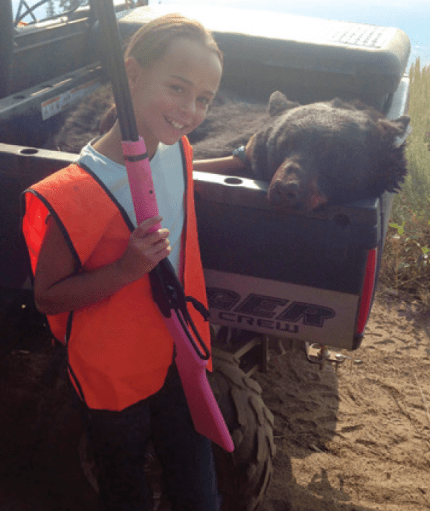 Young girl with pink shotgun poses next to bear body