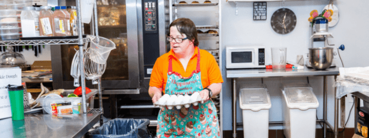 An image of a woman walking through a commercial kitchen. She wears an orange polo shirt and a blue and red apron, and carries a tray of eggs.