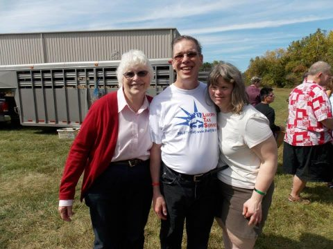 Image of three people standing in a grassy field. On the left, an older caucasian woman stands. It is Andrea Koenker. To her right stands a middle aged caucasian man. It is Donald Bucklew. On the right side of the photo stands a caucasian woman with Down Syndrome. It is Mandy. In the background, more people stand behind them.