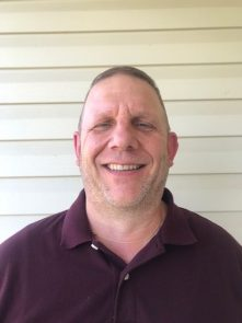 Image of Jim Stevenson. A middle aged Caucasian man smiles at the viewer. He is wearing a maroon polo shirt.