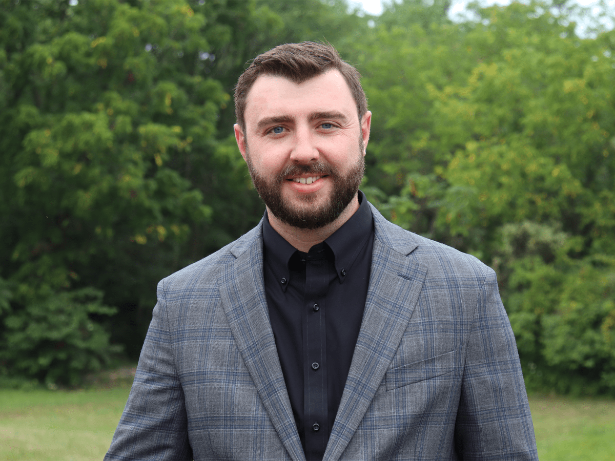 Image of Jake Wharton. A caucasian man wearing a black button up shirt and a gray blazer stands smiling at the camera. He has brown hair and a brown beard. Behind him is a forest.