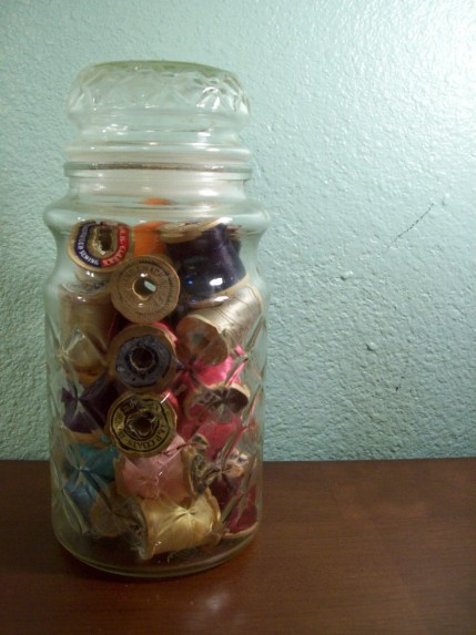 Jar Full of Wooden Spools of Thread