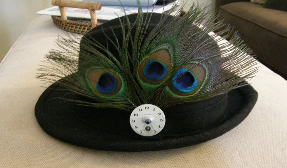 fedora with peacock feather, antique watch dial, and doll eye pin