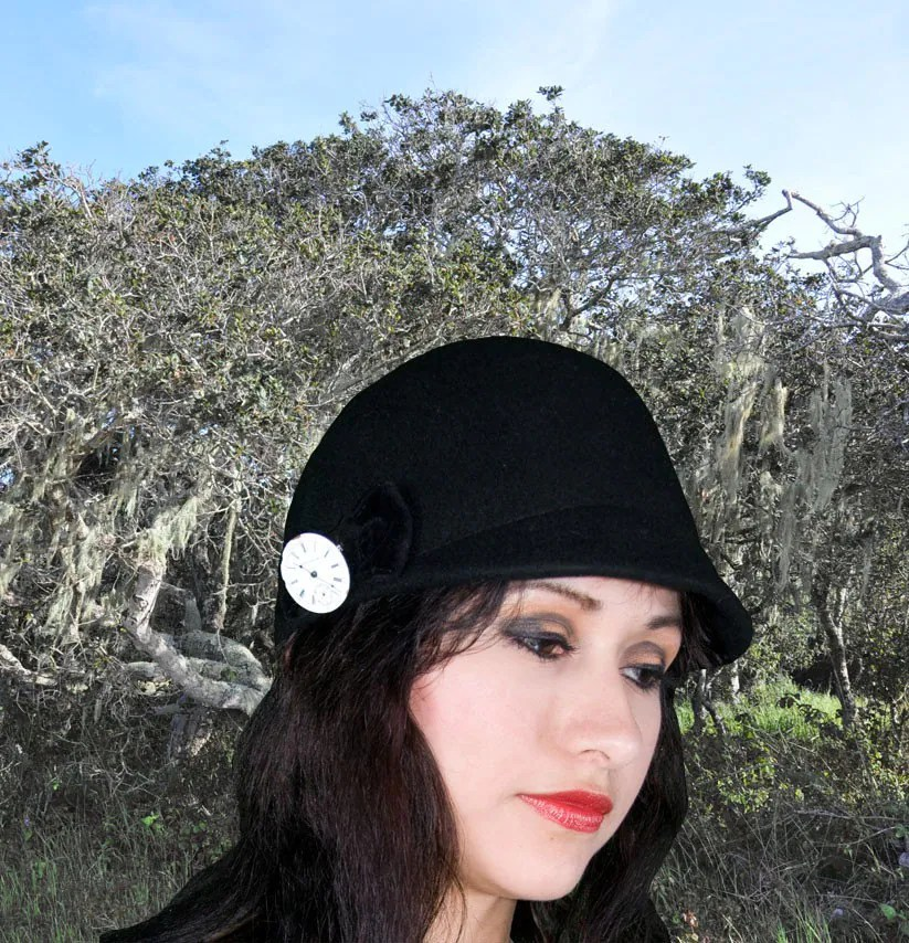 black cloche hat with watch dial pin