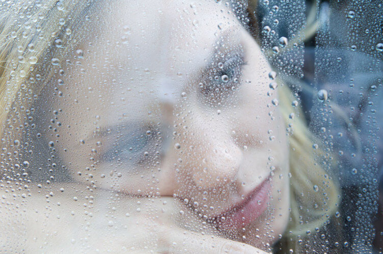 woman behind rain soaked glass