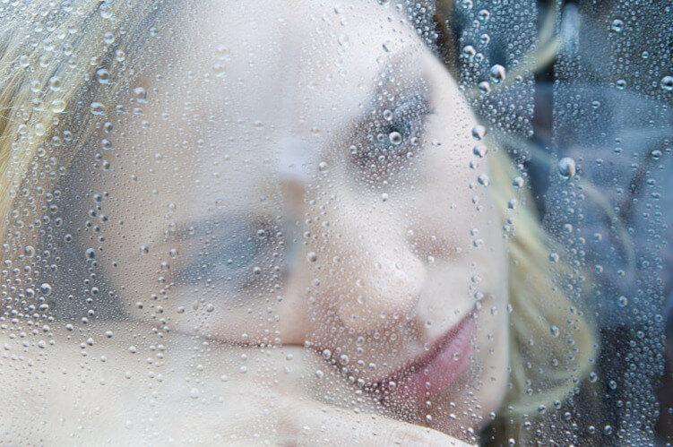 woman behind rain soaked glass