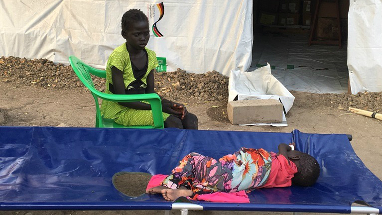 A young girl at a health clinic in South Sudan watches her 3-year-old sister who is sick with cholera (Photo credit: Sam Mednick)