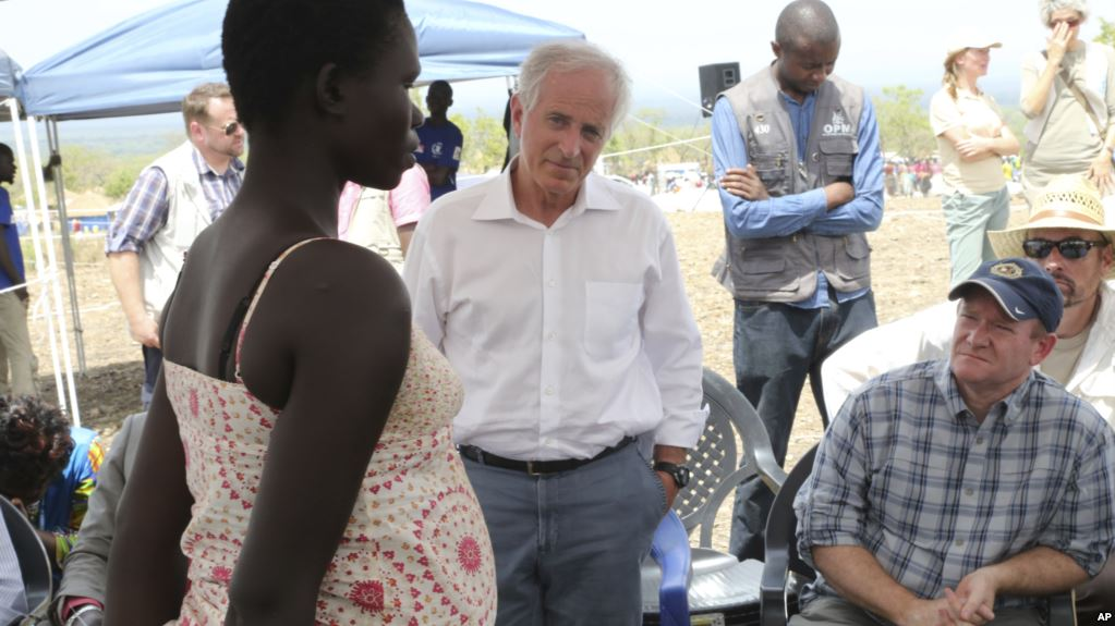U.S Senators Bob Corker, center, and Chris Coons, right, speak with a South Sudanese refugee during a group discussion at the Bidi Bidi refugee settlement in northern Uganda, April 14, 2017.(Photo credit: Justin Lynch/AP)