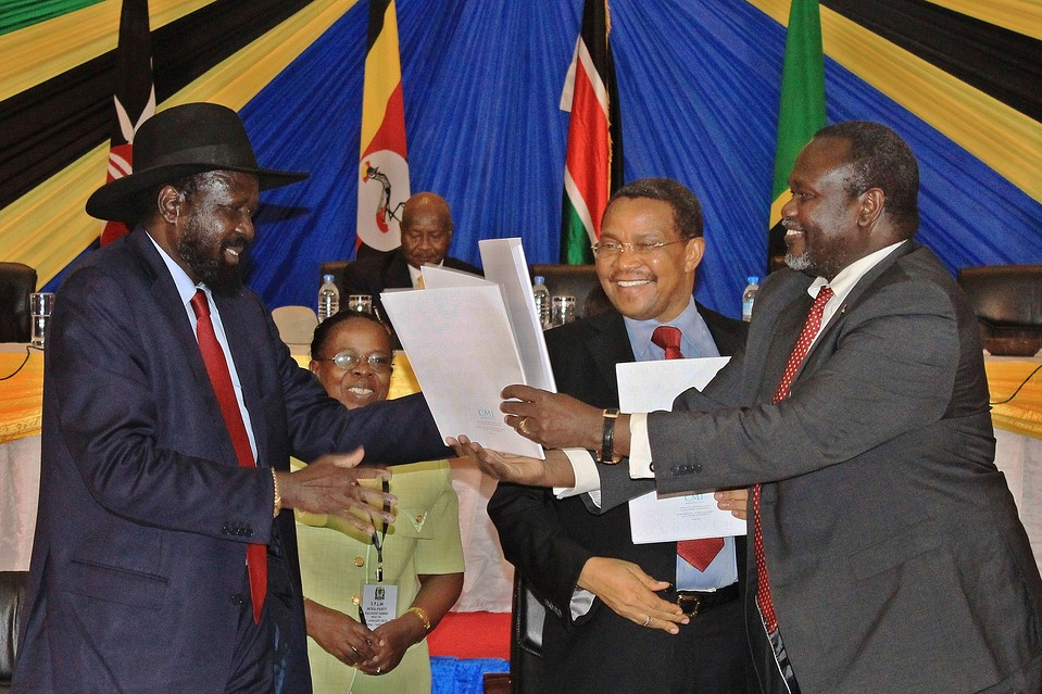South Sudanese President Salva Kiir (left) exchanges documents with rebel leader Riek Machar (right) in Arusha, Tanzania, as Tanzania's President Jakaya kikwete looks on (Photo credit: AFP Getty Images by Nicholas Bariyo on Jan. 22, 2015 11:19 am)