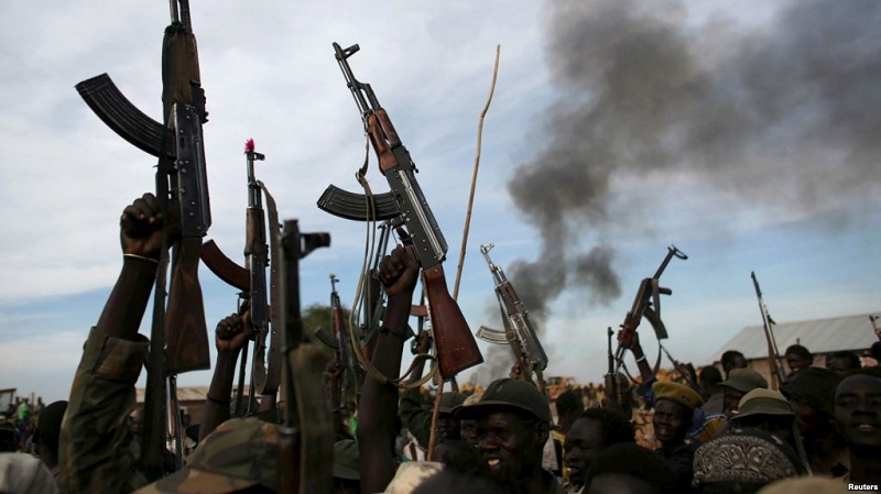 Rebel fighters hold up their rifles as they walk in front of a bushfire in a rebel-controlled territory in Upper Nile state, South Sudan Feb. 13, 2014 (Photo credit: Reuters)