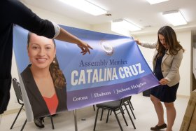 New York Assemblywoman Catalina Cruz examining a decorative banner at her office in Corona, Queens. Although now a citizen, Ms. Cruz grew up undocumented. She said this has informed many of her policy decisions.