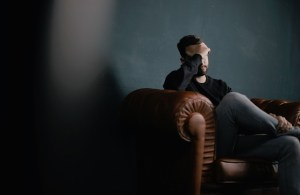 A worried man sitting in an armchair with a hand over his forehead.