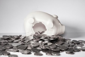 Coins spilling out of a white piggy bank.