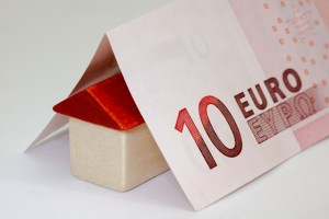 A 10 euro bill folded over a small wooden house.