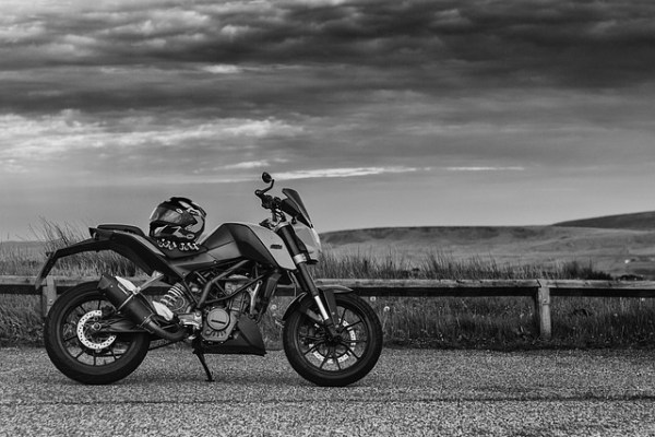 Black and white picture of motorcycle on the road when you think how to move a motorcycle long distance.
