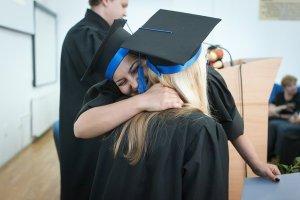 2 graduation students hugging.