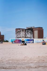 A girl sitting in the sand on Coney Island during a nice sunny day.