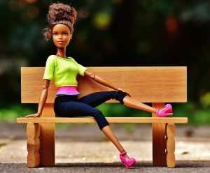 A Barbie sitting on a bench before you place it in a Barbie house made according to DIY decoration ideas for your kids' room.