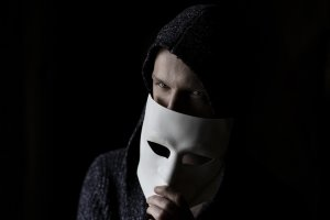 A man in a hoodie revealing his face by taking of the mask