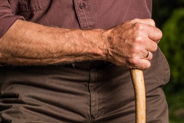A senior holding a walking stick.