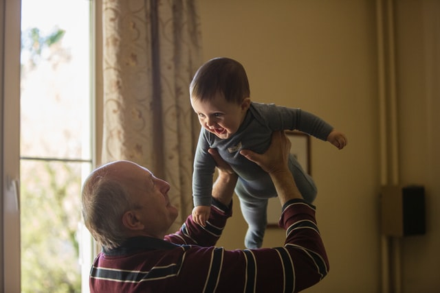 A grandpa holding a baby boy in the air