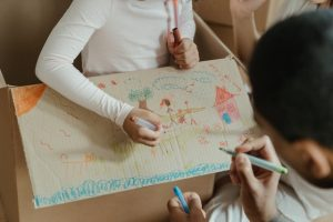Children drawing on a carboard box