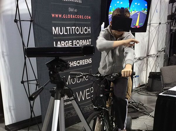 Globacore's PaperDude VR channels an old school arcade game, bringing it up to date by hacking together an indoor resistance bike trainer, Oculus Rift virtual reality head-set, and Microsoft's gesture-recognizing Kinect peripheral.