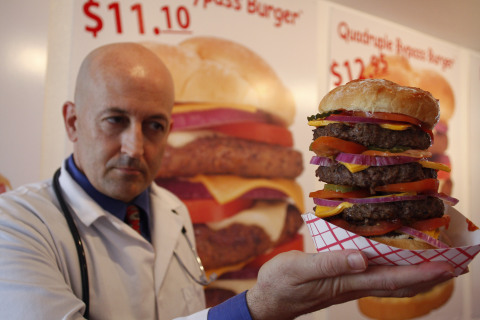 Heart Attack Grill owner Jon poses with a quadruple bypass cheese burger in Chandler, Arizona