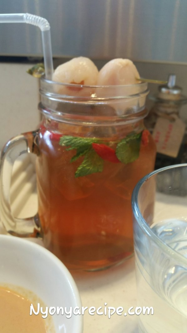 Plum iced tea topped with 2 canned lychees and garnished with mint.
