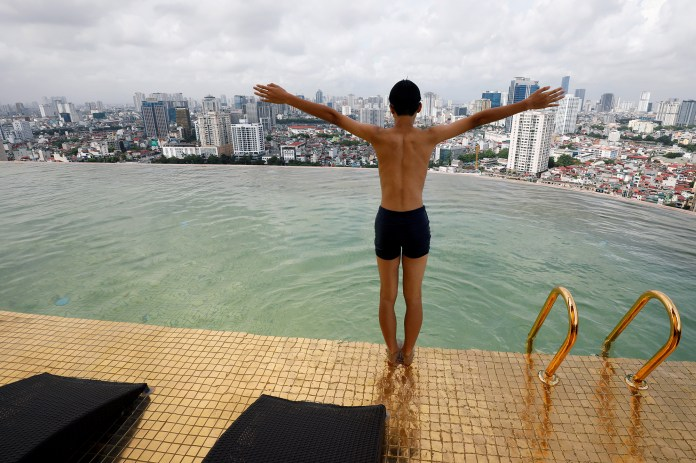 A boy jumps into the water at the gold-plated infinity pool of the newly inaugurated Dolce Hanoi Golden Lake luxury hotel in Hanoi