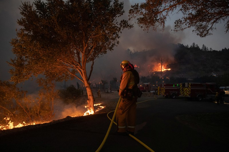 Firefighter protect residence from Glass Fire as it burns a vineyard in Deer Park, California