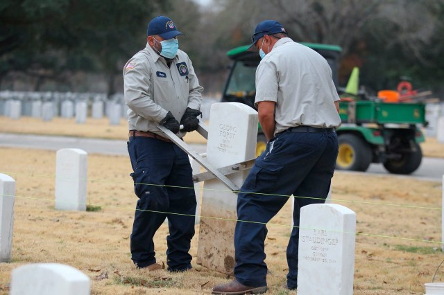 Fort Sam Houston National Cemetery workers remove one of two German WWII graves with Nazi inscriptions and replace them with new headstones.