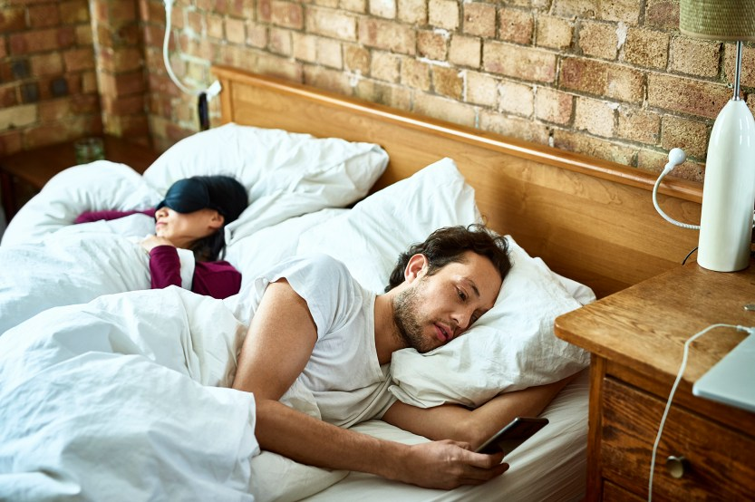 Man sending text message as his girlfriend sleeps in the bed.