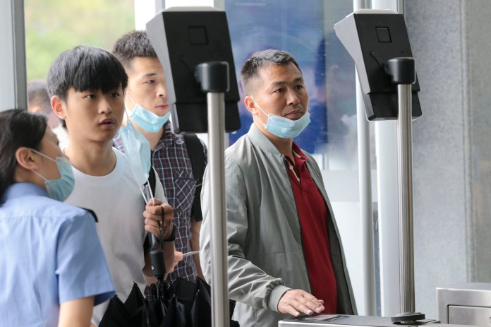 Passengers check-in with their ID cards and facial recognition on e-ticket machines at an entrance of Xi'an Railway Station.