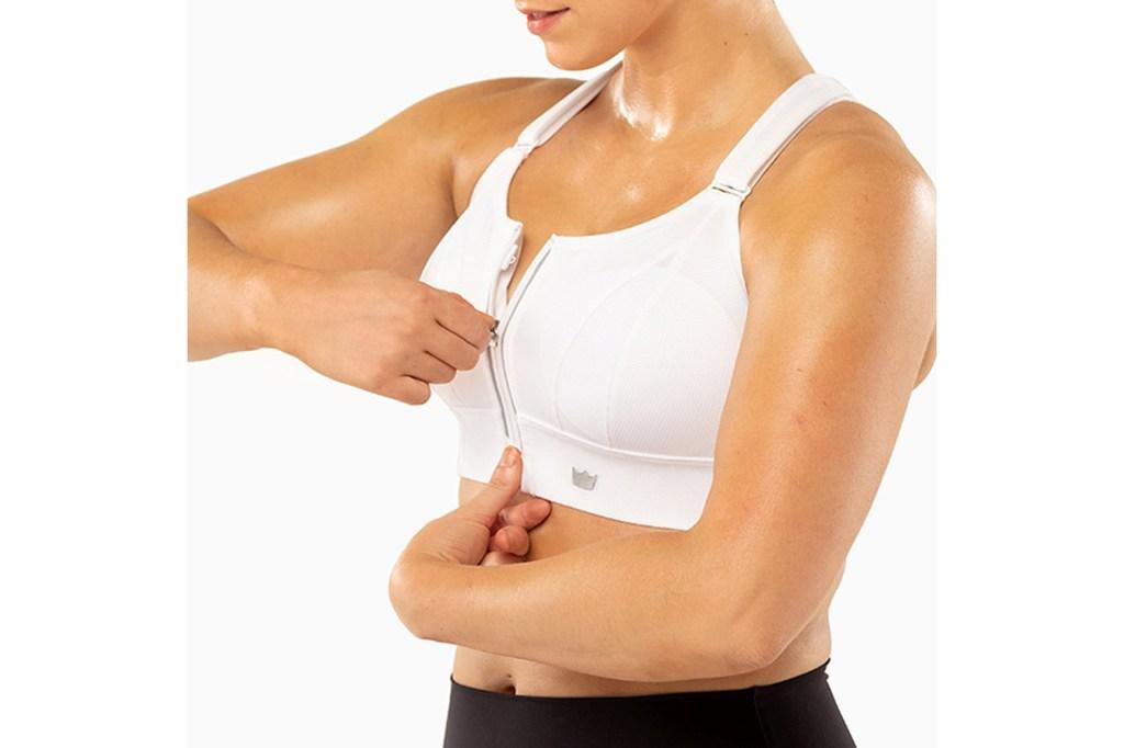 A woman zipping up a white spots bra