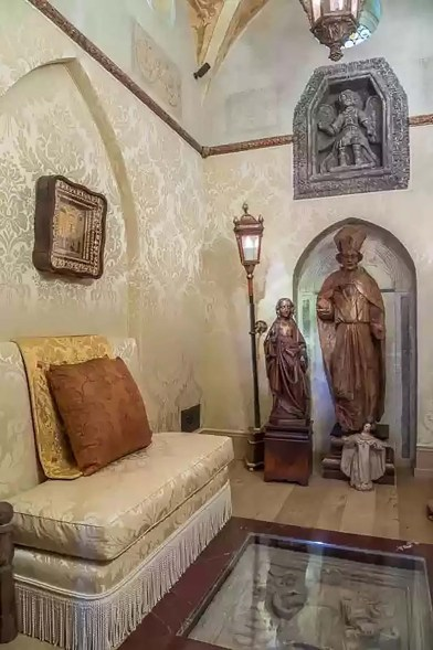 The chapel has detailed cream-colored silk wallpaper and lantern lighting.