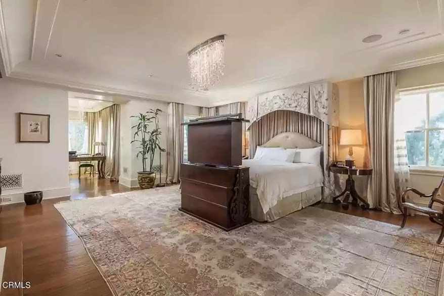 The primary bedroom suite has a cascading chandelier and dual dressing areas.