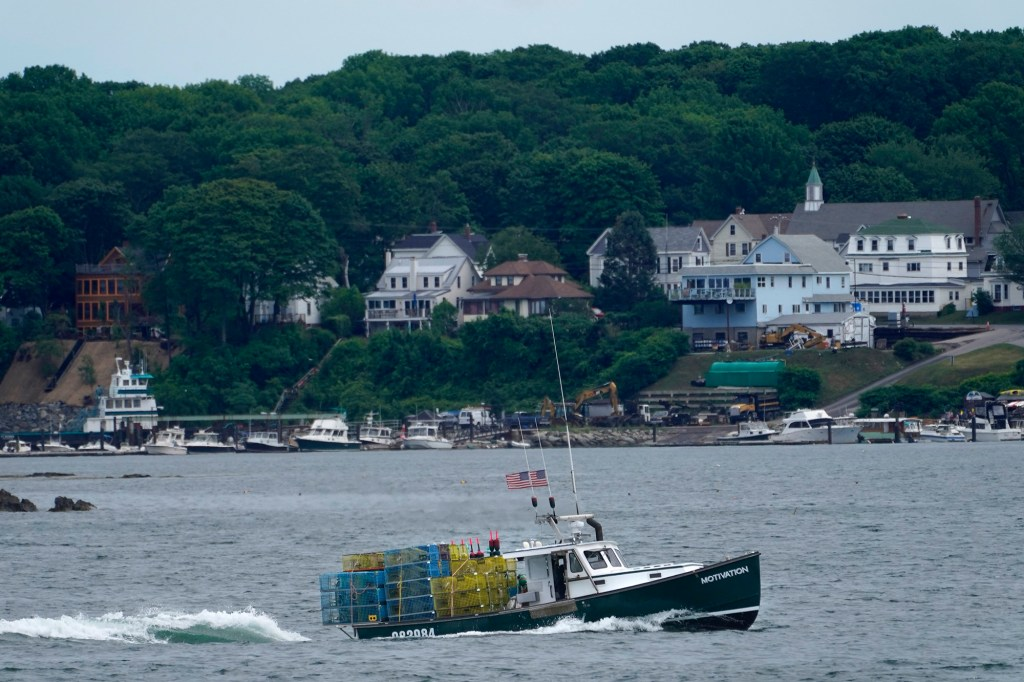 a lobster boat carries a heavy load of traps as it motors out to sea near Peaks Island in Portland, Maine.