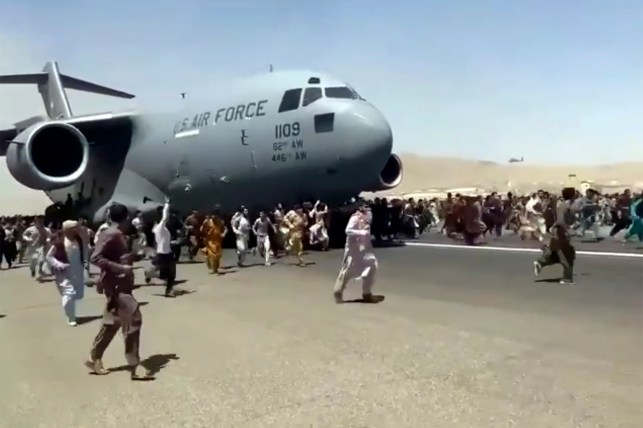 Hundreds of people are running down the runway of Kabul International Airport in Afghanistan with a US Air Force C-17 transport plane.