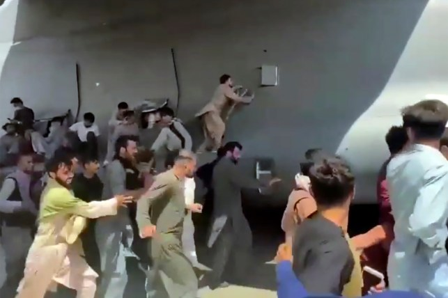 Hundreds of people in Kabul, Afghanistan, run with a US Air Force C-17 transport plane on Monday, August 16, some boarding the plane as it descends from the runway of the international airport.  2021