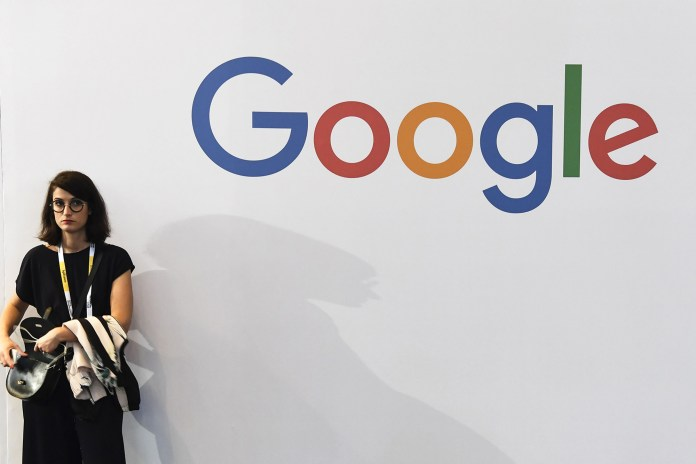 A woman stands beside the logo of the US multinational technology company Google during the VivaTech trade fair, on May 24, 2018 in Paris.