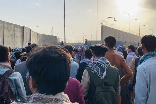 People attempt to get into the Hamid Karzai International Airport, to flee the country, in Kabul, Afghanistan, 23 August 2021