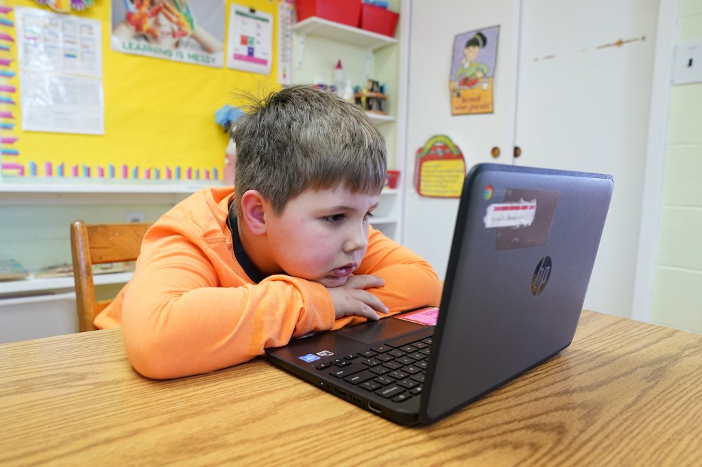 A general view of a public school elementary school student using a laptop to participate in a remote learning class.