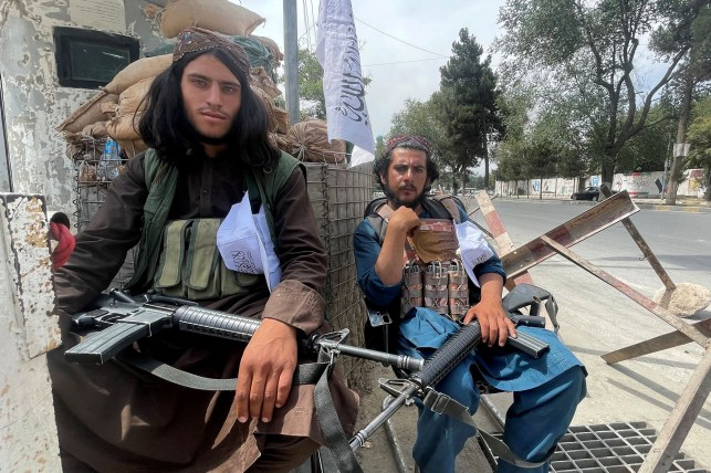 Members of the Taliban sit at a checkpoint in Kabul, Afghanistan.