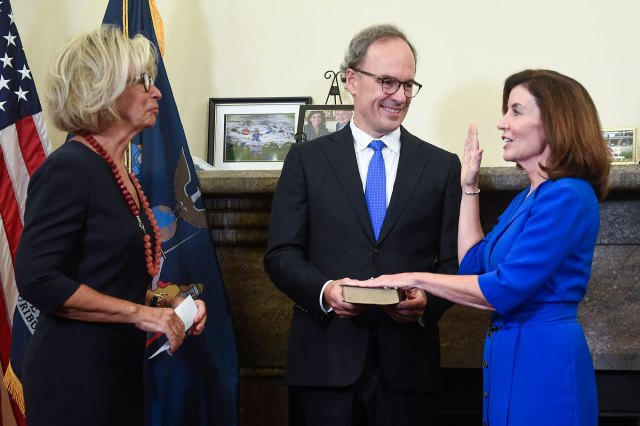 New York Chief Judge Janet DiFiore, left, swears in Kathy Hochul, right, as the first woman to be New York's governor while her husband Bill Hochul holds a bible during a swearing-in ceremony in the Red Room at the state Capitol.