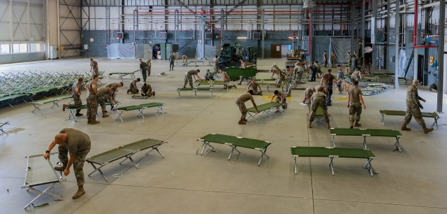 Air Force airmen setting up cots at a hanger in Ramstein Air Base in Germany to lodge evacuees from Afghanistan.