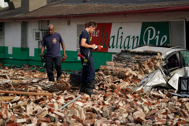 New Orleans Firefighters assess damages as they look through debris after a building collapsed from the effects of Hurricane Ida.
