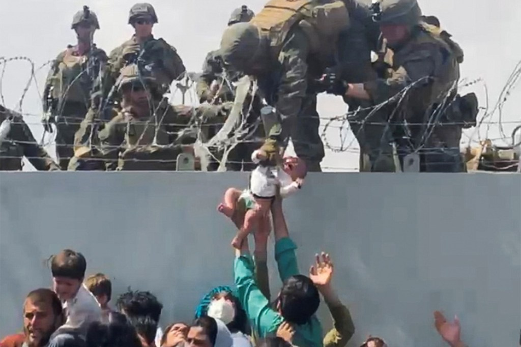 A baby is given to the American Army over the perimeter wall of the airport in Kabul, Afghanistan, on August 19, 2021.